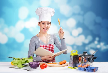 Photo for Portrait of a woman in chef's hat reading cookbook and raising up a spoon, with blue boke background - Royalty Free Image