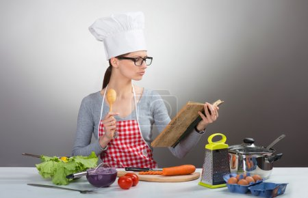 Photo for Portrait of a pretty serious woman in chef's hat cooking with old cookbook, on gray background - Royalty Free Image