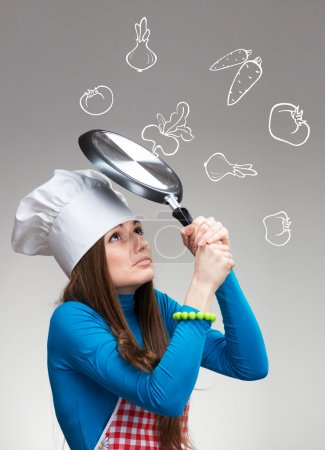 Photo for Funny portrait of a woman with the pan protecting herself from the falling drawn vegetables - Royalty Free Image