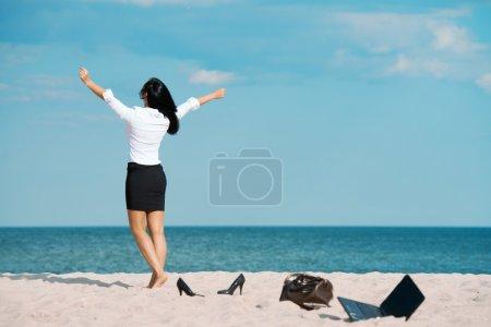 Businesswoman walks towards to sea leaving her lap...