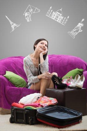 Photo pour Souriante fille rêvant de vacances, avec des points de repère peints sur fond gris - image libre de droit