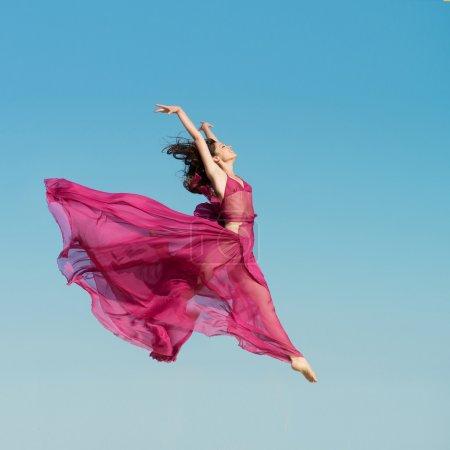 Photo pour Fille en robe cramoisi aérée sautant dans les airs, fond bleu ciel - image libre de droit