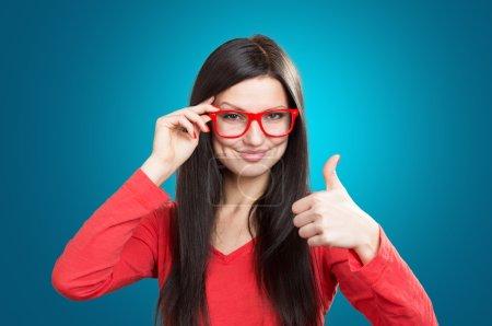 Photo pour Verticale d'une jolie fille de sourire avec un pouce vers le haut, projectile de studio sur le fond bleu - image libre de droit