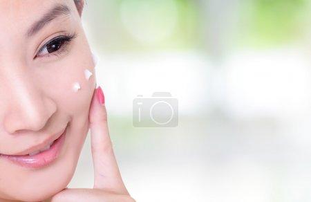 Half face of woman taking cream