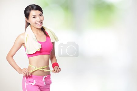 Woman smile measuring shape of waist