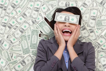 business woman excited lying on money