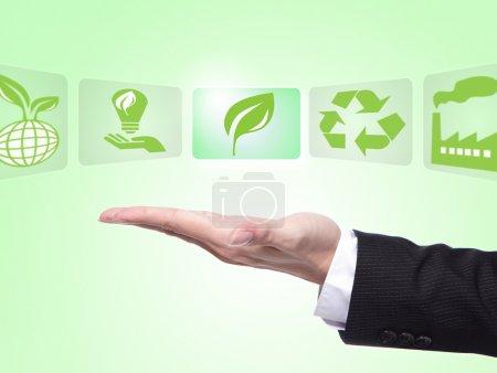 Photo pour Vert eco concept d'icônes, paume de main homme affaires détenant toutes sortes d'icône sur eco avec fond vert - image libre de droit