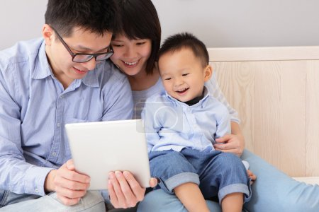 Photo for Closeup of a happy, family of mother, father, son sitting on bed at home having fun using a tablet pc, asian - Royalty Free Image