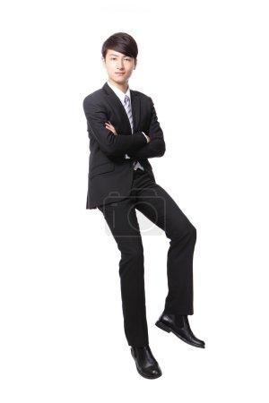 Photo pour Homme d'affaires réussie assis sur quelque chose et regardez vous isolé sur fond blanc, modèle masculin asiatique - image libre de droit
