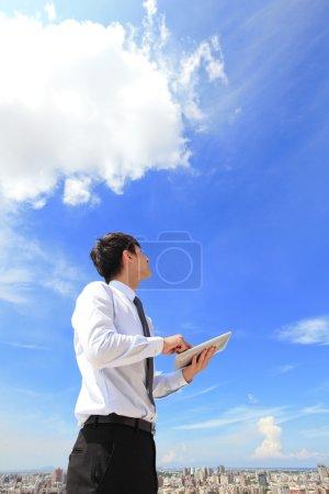 Photo pour Homme d'affaires jeune utilisant tablet pc et regarder vers le ciel bleu et avec le paysage urbain dans le fond, les entreprises et les concept informatique de nuage en nuage - image libre de droit