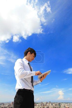 Photo pour Homme d'affaires jeune utilisant tablet pc avec le paysage urbain et le nuage dans le fond, le business et le nuage informatique concept - image libre de droit