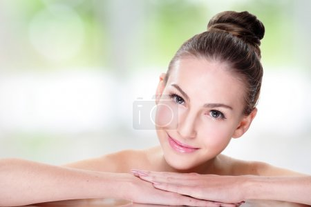 Photo for Close up portrait of beautiful young woman face while lying. Isolated on green background. Skin care or spa concept - Royalty Free Image