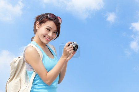 Happy woman traveler taking photo by camera