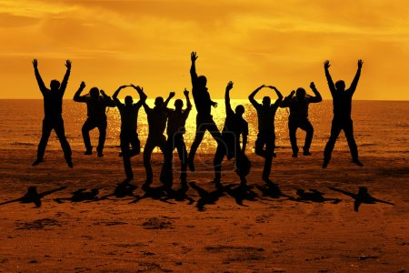 Male friends are having fun at summer and jumping up on the sunset near the sea putting their hands up to the orange sky