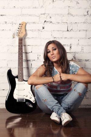 Photo pour Photo de fille agréable musicien assis sur le plancher en bois - image libre de droit