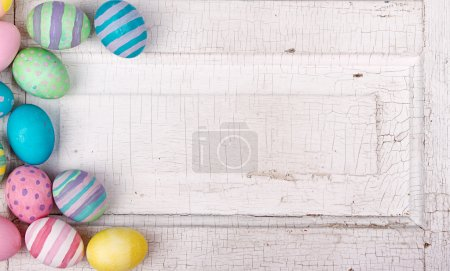 Photo for Easter eggs painted in pastel colors on a white cracked antique background - Royalty Free Image