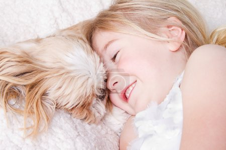 Girl laying with shih tzu dog