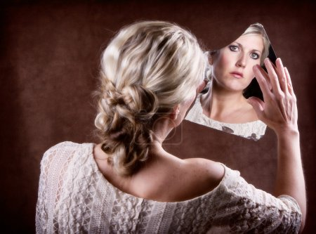 Photo for Woman looking into a broken mirror touching it with her hand, with back of head showing - Royalty Free Image