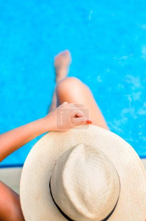Young woman enjoying the sun at the pool while holding a hat