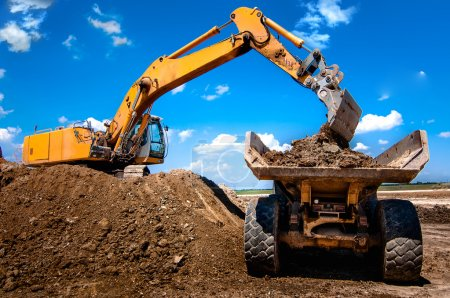 Excavator loading dumper truck tipper in sandpit