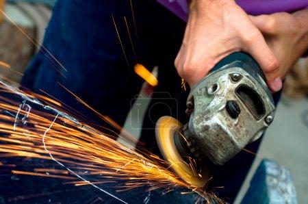 Photo pour L'industrie lourde acier travailleur avec meuleuse d'angle au service de la voiture - image libre de droit