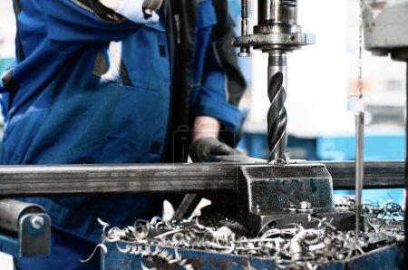 Photo pour Tehnician industriel travaillant sur une machine de forage - faire un trou dans une barre métallique - image libre de droit