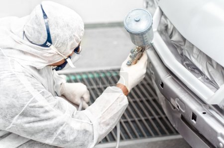 Photo for Auto mechanic engineer painting a grey car in a special booth - Royalty Free Image