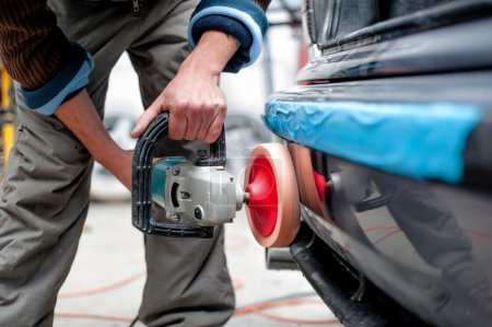 Professional mechanic using a power buffer machine for cleaning the body of a car