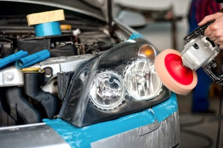 Auto mechanic working on polishing a car headlight with power buffer machine in car care system