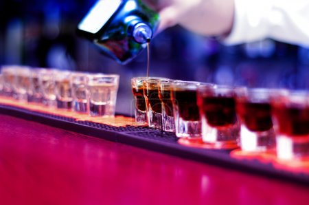 Photo pour Barman verser une boisson alcoolisée forte dans de petits verres sur le bar, coups de feu - image libre de droit