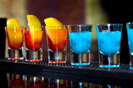 Several alcoholic shots of diferent drinks at a party in a nightclub on the counter