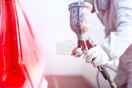 Foto de Primer plano de la pistola con pintura roja pintando un coche en especial booth - Imagen libre de derechos