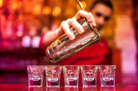 Bartender pouring strong alcoholic drink into shots at nightclub