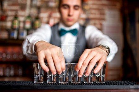 Photo pour Barman préparer des photos pour un cocktail sur le bar - image libre de droit