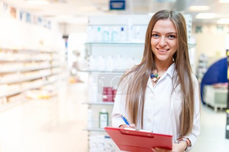 Portrait of smiling young blonde pharmacist at drug store with red clipboard