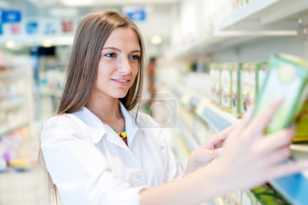 Portrait of beautiful blonde female pharmacist reading a label in drug store