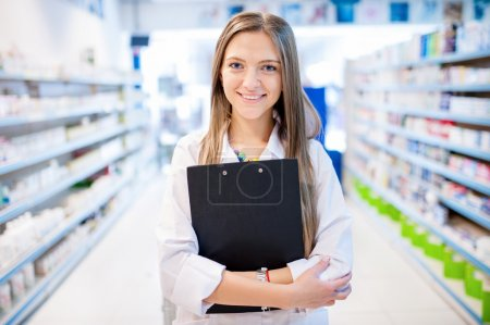 Blonde pharmacist with clipboard and prescription drugs