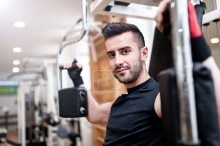 Handsome man working out at gym, daily chest exercise routine. Fitness concept
