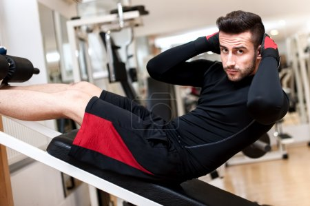 Handsome muscular man doing sit-ups on a incline bench at fitness center and gym