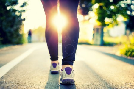 Close-up of woman athlete feet and shoes while running in park. Fitness concept and welfare with female athlete joggin in city park