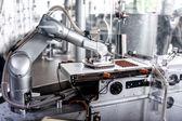 Automatické robotické ruky stěhování a příprava kousíčky čokolády na továrnu na čokoládu. Průmyslová továrna na čokoládu s automatickým robotické ruky