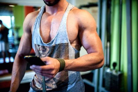 Close-up of Muscular man on a break from workout, checking mail on telephone