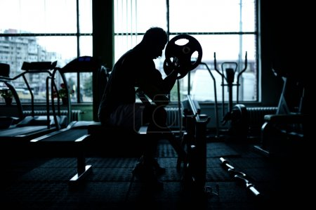 Silhouette of an athletic man working out at gym. Fitness bodybuilder training in the gym