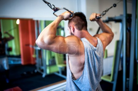 Young, muscular man, bodybuilder working out in gym. Fitness concept on healthy life, sports and gym