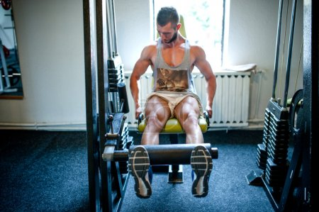 Bodybuilder working legs at gym, fitness concept of a healthy life