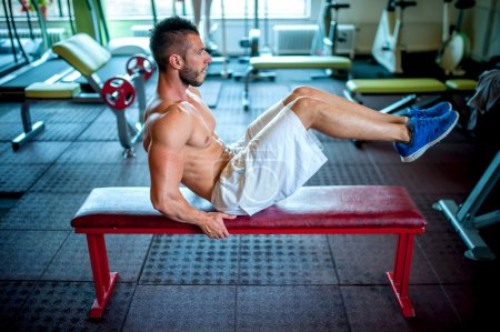 athletic fitness man working the abdomen at gym
