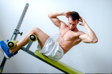 Photo for Handsome muscular man doing sit-ups on a incline bench at fitness center or gym - Royalty Free Image