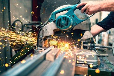 Photo pour Travailleur industriel utilisant une scie à mitre composée avec lame circulaire pour couper le métal et le plastique - image libre de droit