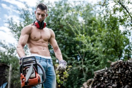 Portrait of sexy man with chainsaw and protective gear ready for cutting wood