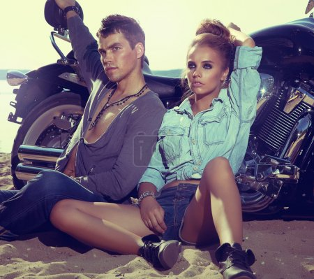 Photo for Two and bike - fashion woman and man sitting by motorbike and resting. Adventure and vacations concept - Royalty Free Image